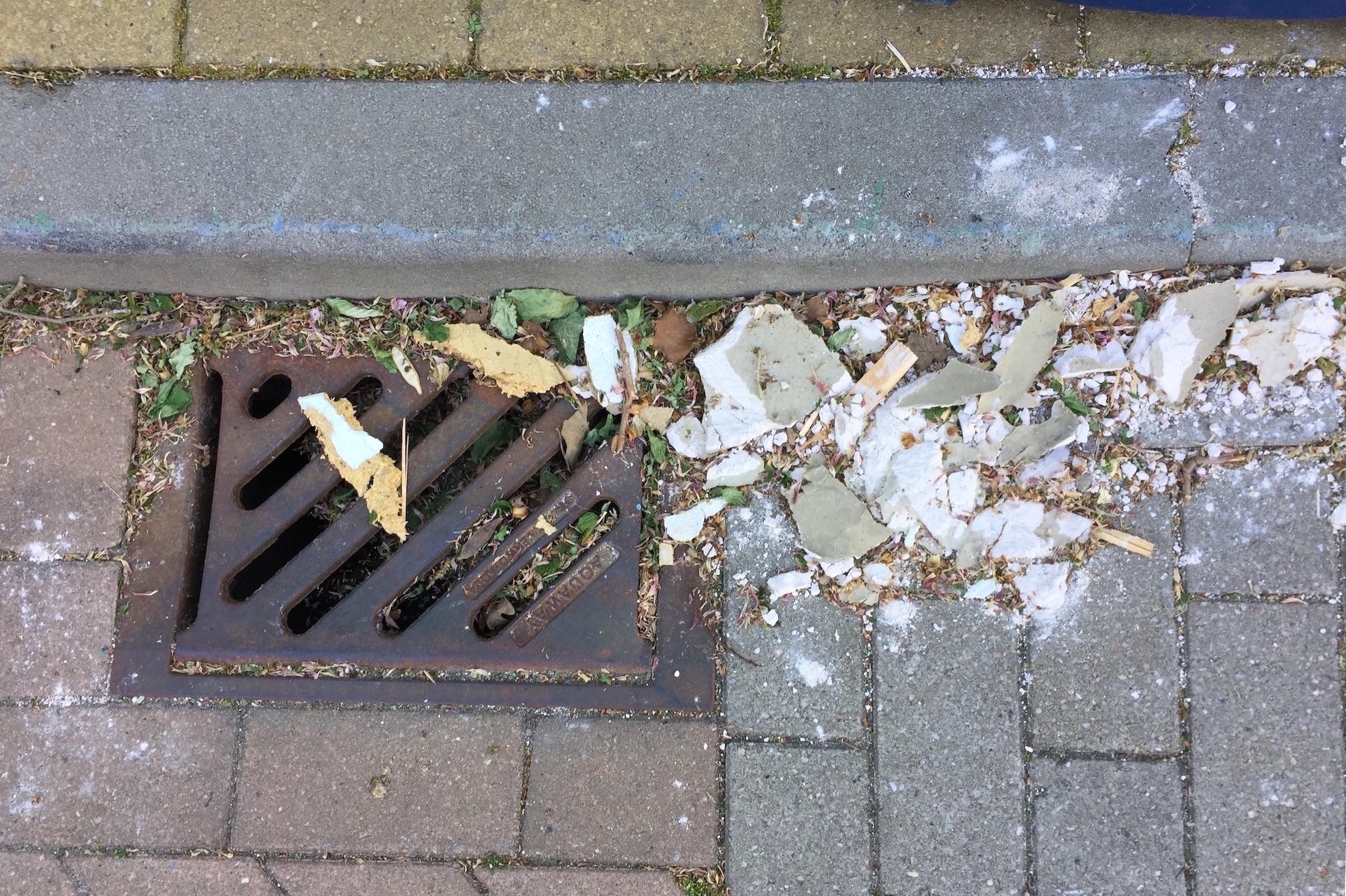 Het vuil dat bij een straatkolk ligt kan in het riool terecht komen.
